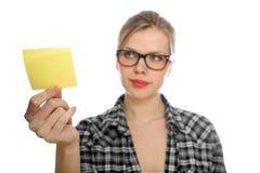 La ragazza dell'allievo con i vetri cattura una nota gialla Fotografia Stock Libera da Diritti
