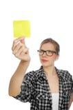 La ragazza dell'allievo con i vetri cattura una nota gialla Immagini Stock