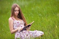 La ragazza dell'allievo si siede su prato inglese e legge il manuale. Fotografia Stock Libera da Diritti