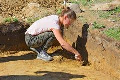 La ragazza dell'archeologo allinea la parete ed il fondo dello scavo con una spatola Immagine Stock Libera da Diritti