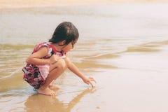 La ragazza dell'asiatico sta attingendo la spiaggia immagini stock