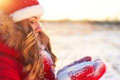 La ragazza dell'inverno nel rosso soffia nelle palme della neve nel sole caldo del tramonto immagine stock libera da diritti