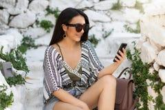 La ragazza della città si siede sulle scale bianche e guarda il suo telefono cellulare immagini stock