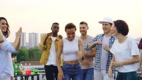 La ragazza della corsa abbastanza mista sta ballando con gli amici e sta ridendo godendo del partito del tetto Spettacolo, facent stock footage