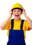La ragazza della costruzione tiene il suoi cappello duro e grido Immagini Stock Libere da Diritti