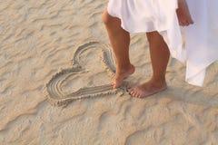 La ragazza della gamba assorbe il cuore della sabbia Immagine Stock