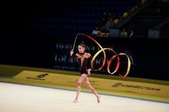 La ragazza della ginnasta esegue alla concorrenza della ginnastica ritmica Fotografia Stock Libera da Diritti