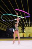 La ragazza della ginnasta esegue alla concorrenza della ginnastica ritmica Fotografia Stock