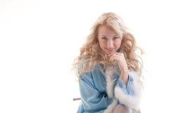 La ragazza della neve in cappotto di pelliccia blu si siede e sorride Fotografie Stock