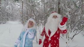 La ragazza della neve della nipote e di Santa nella foresta innevata nel pomeriggio invia i baci dell'aria stock footage