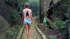 La ragazza della parte cammina lungo la vecchia pista di pietra in parco spesso video d archivio