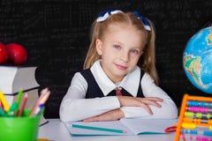La ragazza della scolara con i libri si avvicina alla lavagna della scuola Immagine Stock Libera da Diritti