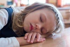 La ragazza della scuola che dorme alla scuola è sonno allo scrittorio allievo Studio dell'allievo Immagini Stock Libere da Diritti