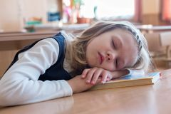 La ragazza della scuola che dorme alla scuola è sonno allo scrittorio allievo Studio dell'allievo Immagine Stock