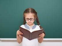 La ragazza della scuola ha letto il libro, posante al consiglio scolastico, spazio vuoto, concetto di istruzione Immagini Stock