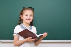 La ragazza della scuola ha letto il libro, posante al consiglio scolastico, spazio vuoto, concetto di istruzione Immagini Stock Libere da Diritti