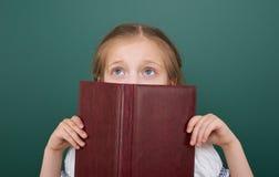 La ragazza della scuola ha letto il libro, posante al consiglio scolastico, spazio vuoto, concetto di istruzione Fotografia Stock