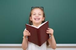 La ragazza della scuola ha letto il libro, posante al consiglio scolastico, spazio vuoto, concetto di istruzione Fotografie Stock