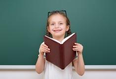 La ragazza della scuola ha letto il libro, posante al consiglio scolastico, spazio vuoto, concetto di istruzione Immagine Stock