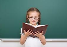 La ragazza della scuola ha letto il libro, posante al consiglio scolastico, spazio vuoto, concetto di istruzione Immagine Stock Libera da Diritti