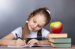 La ragazza della scuola della ragazza scrive in un taccuino mentre si siede ad uno scrittorio Fotografia Stock