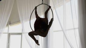 La ragazza della siluetta esegue gli elementi acrobatici nell'anello dell'aria archivi video