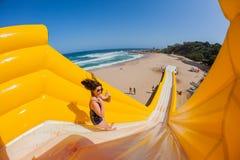 La ragazza della spiaggia salta lo scorrevole di alta marea di giri Immagini Stock