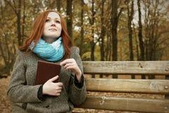 La ragazza della testarossa con il libro si siede su un banco nel parco della città, stagione di caduta Immagine Stock