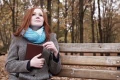 La ragazza della testarossa con il libro si siede su un banco nel parco della città, stagione di caduta Immagini Stock Libere da Diritti
