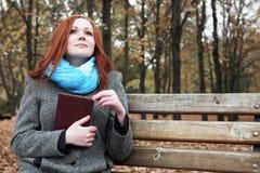 La ragazza della testarossa con il libro si siede su un banco nel parco della città, stagione di caduta Fotografie Stock