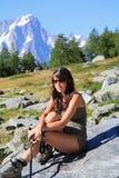 La ragazza della viandante si siede su una pietra della montagna immagine stock
