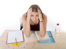 La ragazza dello studente di college che studia per l'esame dell'università si è preoccupata nella sensibilità di sforzo stanca e Immagine Stock