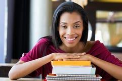 La ragazza dello studente si appoggia la pila di libri Fotografia Stock Libera da Diritti