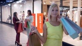 La ragazza di acquisto in vestito giallo con i sacchi di carta sta su un fondo di due ragazze con gli acquisti in centro commerci archivi video