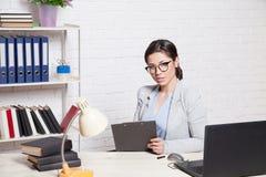 La ragazza di affari si siede ad un computer nelle cartelle della carta dell'ufficio Immagine Stock