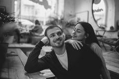 La ragazza di amore tiene la sua mano sulla spalla del suo ragazzo che si siede alla tavola nel caff? romantico accogliente Il ne fotografia stock