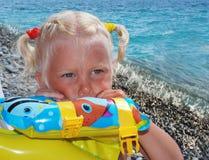 La ragazza di 3 anni, la bionda, su una spiaggia del mare immagine stock