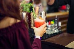 La ragazza di Backview passa a tenuta il vetro di plastica con il cocktail rosso con il contatore della barra sui precedenti Svag Fotografia Stock