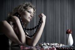 La ragazza di bellezza si siede alla tabella con gli accessori Immagine Stock