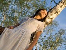 La ragazza di bellezza si siede sull'albero di betulla   fotografia stock libera da diritti
