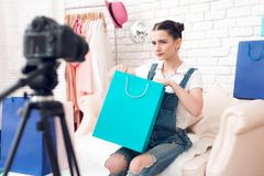 La ragazza di blogger di modo con compone la borsa variopinta dei presente alla macchina fotografica fotografia stock