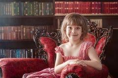 La ragazza di cinque anni sveglia si siede su una poltrona rossa fotografia stock libera da diritti