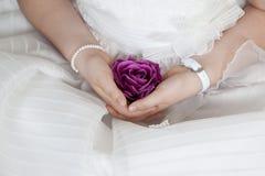 La ragazza di comunione si è vestita nel bianco con un fiore porpora nei suoi handas fotografie stock