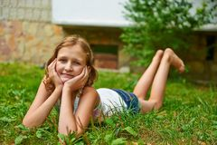 La ragazza di dodici anni si trova sull'erba e sul sorridere Fotografie Stock Libere da Diritti