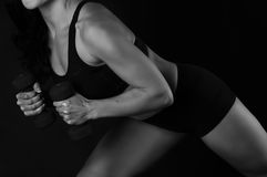 La ragazza di forma fisica con le teste di legno su un fondo nero negli sport posa Fotografie Stock Libere da Diritti