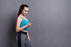 La ragazza di forma fisica in cuffie sceglie la musica sul telefono Fotografia Stock Libera da Diritti