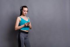 La ragazza di forma fisica in cuffie sceglie la musica sul telefono Fotografia Stock