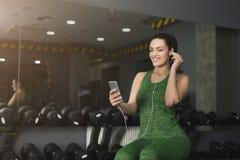 La ragazza di forma fisica in cuffie sceglie la musica sul telefono Immagini Stock Libere da Diritti