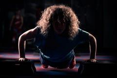 La ragazza di forma fisica sta risolvendo con passo passo Forte castana con capelli ricci che fanno aerobica su passo passo Forte Immagini Stock Libere da Diritti