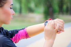 La ragazza di Ftitness mette l'inseguitore del cronometro sul suo polso durante il funzionamento fotografia stock libera da diritti